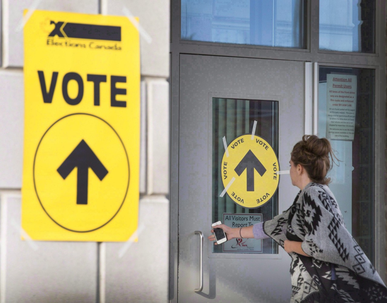 A woman enters Maple High School in Vaughan, Ont., to cast her vote in the Canadian federal election on Oct. 19, 2015. (Peter Power / THE CANADIAN PRESS)