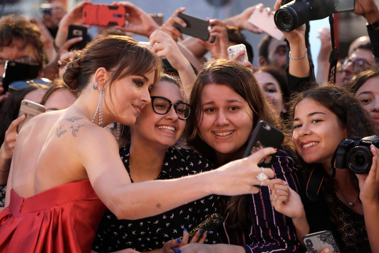 Dakota Johnson takes a selfie with fans at the 'Suspiria' premiere in Venice, on Sept. 1, 2018. (AP / Kirsty Wigglesworth)
